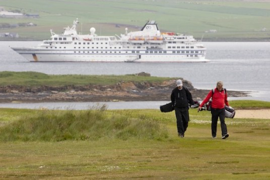 RCGS Resolute in the harbour with golfers in the foreground, Stromness, Orkney Islands. (Image: Boomer Jerritt/One Ocean Expeditions)