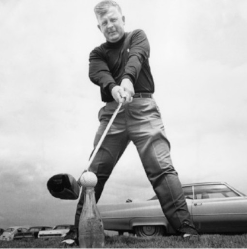 Golfer Moe Norman tees up the ball for a drive