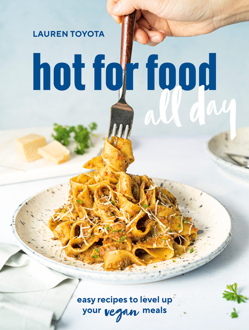 The cover of Lauren Toyota's new vegan cookbook titled hot for food; the photo is of a fork over a plate of pasta with pasta wrapped around the end of the fork