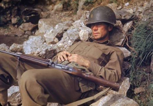 American soldier sleeping on a pile of rocks during the drive towards Rome, WWII