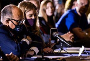 Image de Rudy Giuliani tenant son téléphone devant un haut-parler avec Trump au bout d fil.