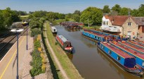 Lower Heyford. Canal and railway running in parallel. On the right Oxfordshire Narrowboats. More of note to passersby is Kizzie's tearoom dispensing antidotes to afternoon napping of tea and cakes.
