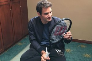 Roger Federer mirando su raqueta Wilson
