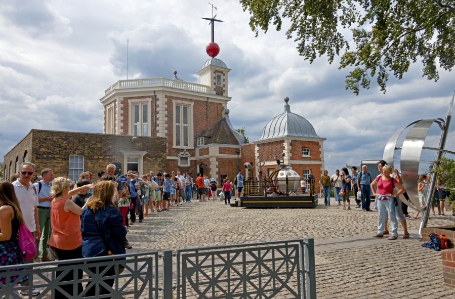 Tourists take pictures at the Greenwich Prime Meridian