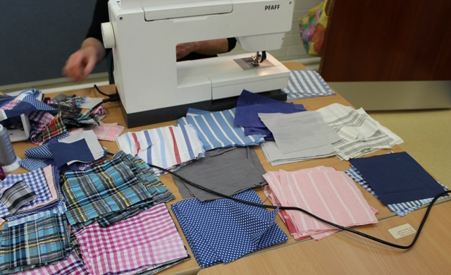 Beres cut out squares from men's shirts ready to piece into a quilt