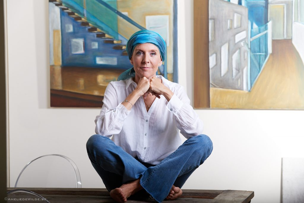 Delphine Remy sitting on a table with a chemo scarf