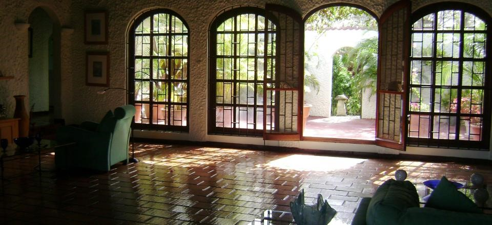 "The living room opens onto 2 courtyards. The house is called ""The Arches"" because of the beautiful windows.."
