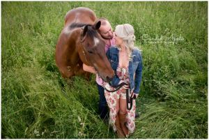 A couple standing in a hay field holding a horse