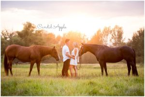 Couple standing with their horses, holding each other during golden hour