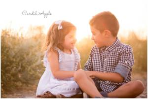 Little boy and girl looking at each other at sunset