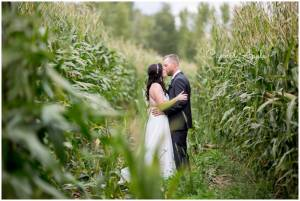 A couple standing in a corn field kissing