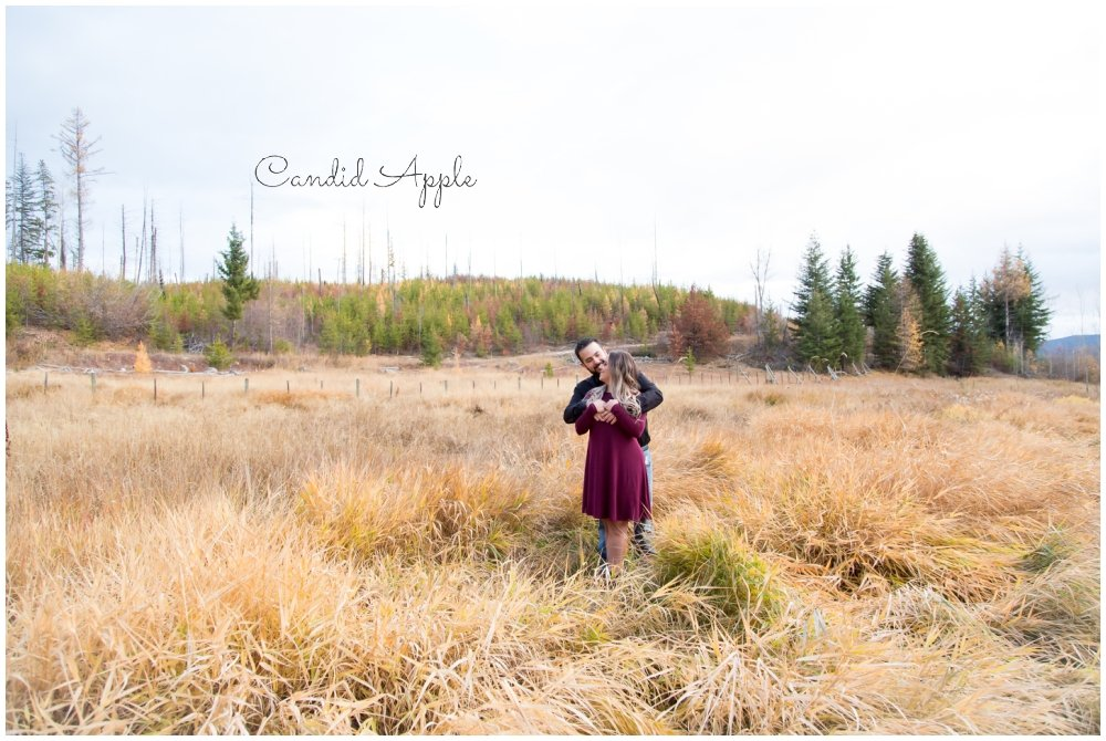 A couple hugging in a grassy field during their engagement session
