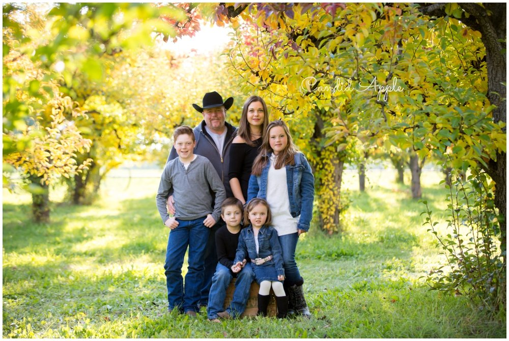 A family standing together in an orchard in the Fall