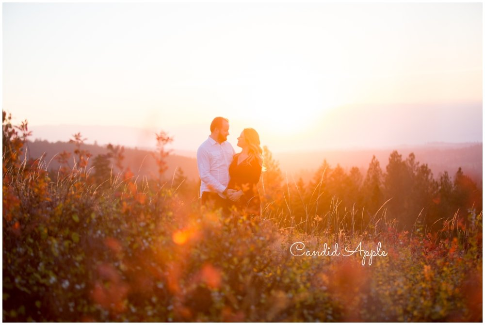 A couple standing in a field looking at their soon to be baby at sunset