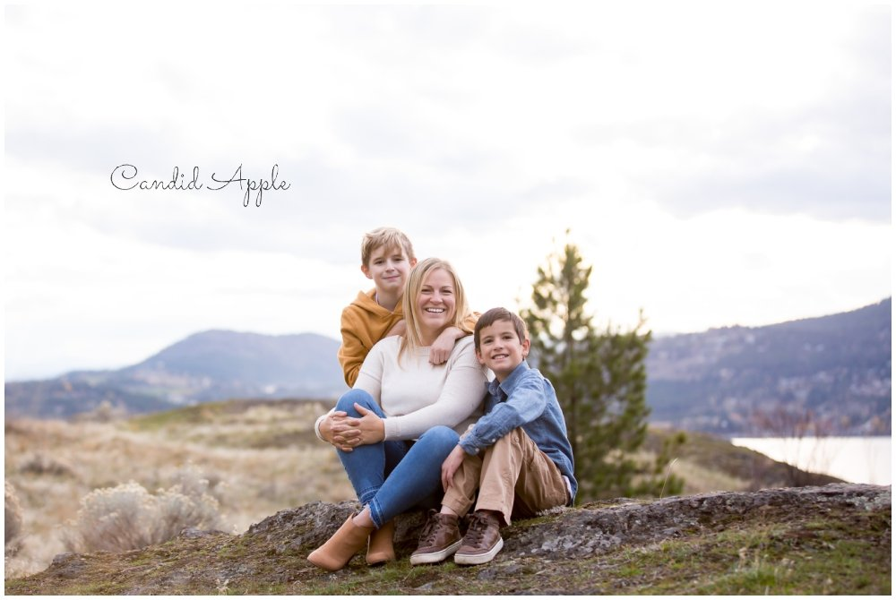 A family of three sitting on a mountaintop in Fall