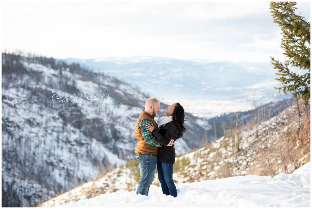 A couple standing on a mountaintop laughing together