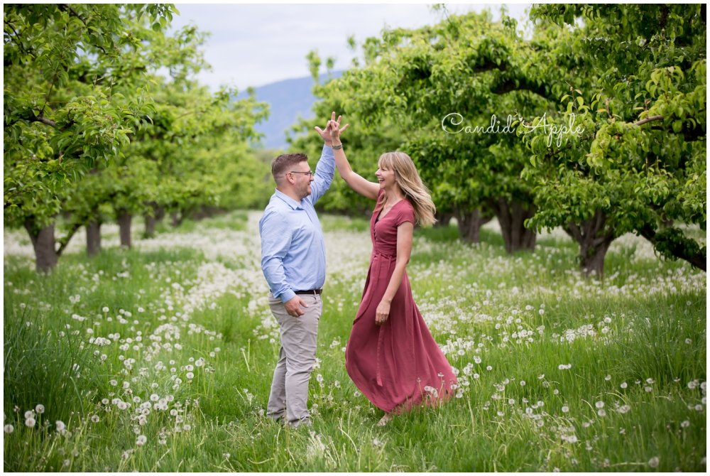 A couple danicing in an orchard with white dandelions