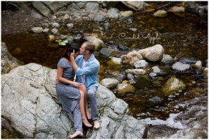 A couple sitting on the rocks by a waterfall