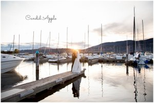 A bride and groom standing in fron tof a sunset