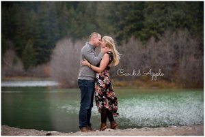 a couple kissing in front of a beautiful lake