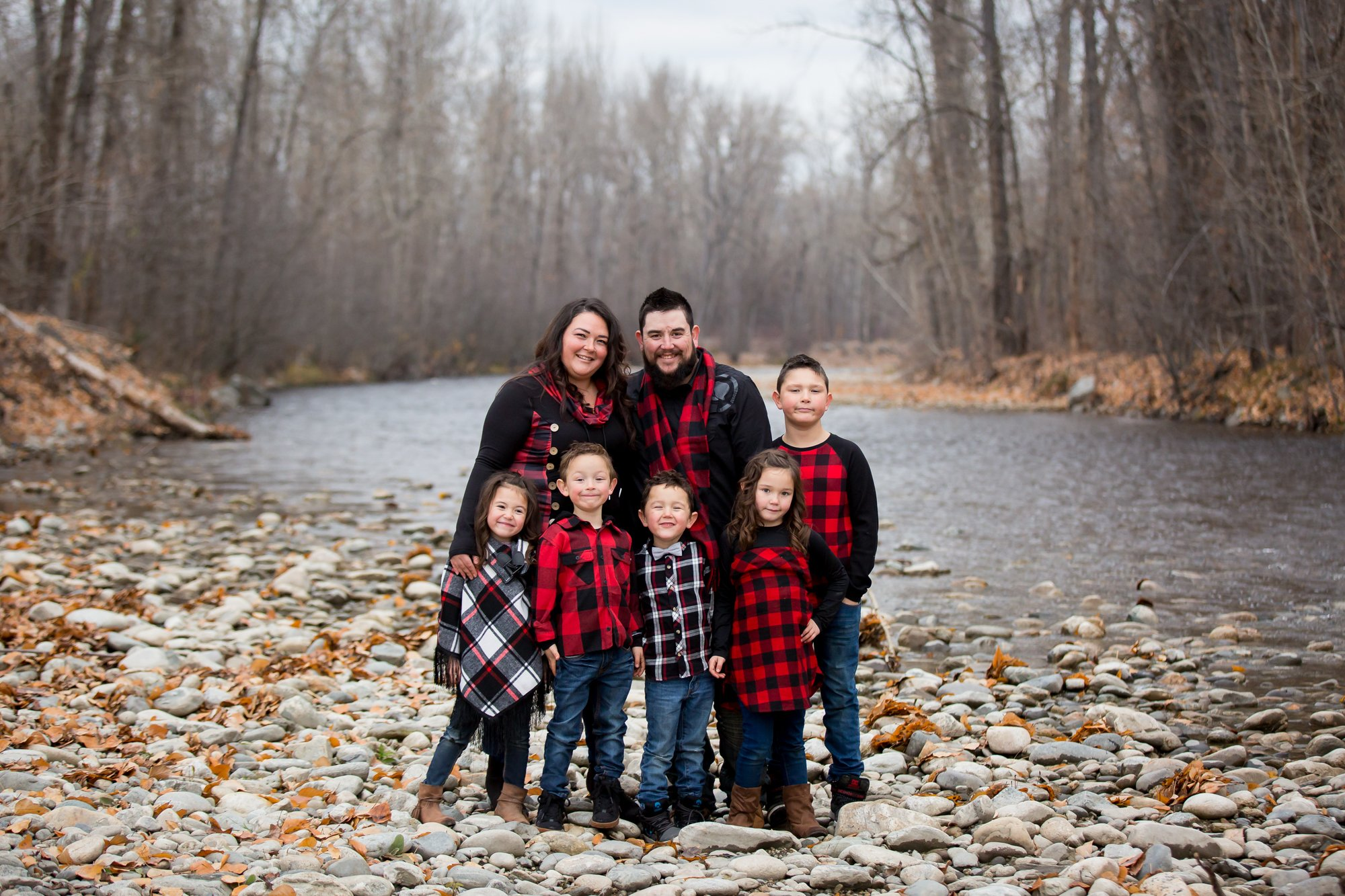 A family standing together in a creekside wearing red plaid
