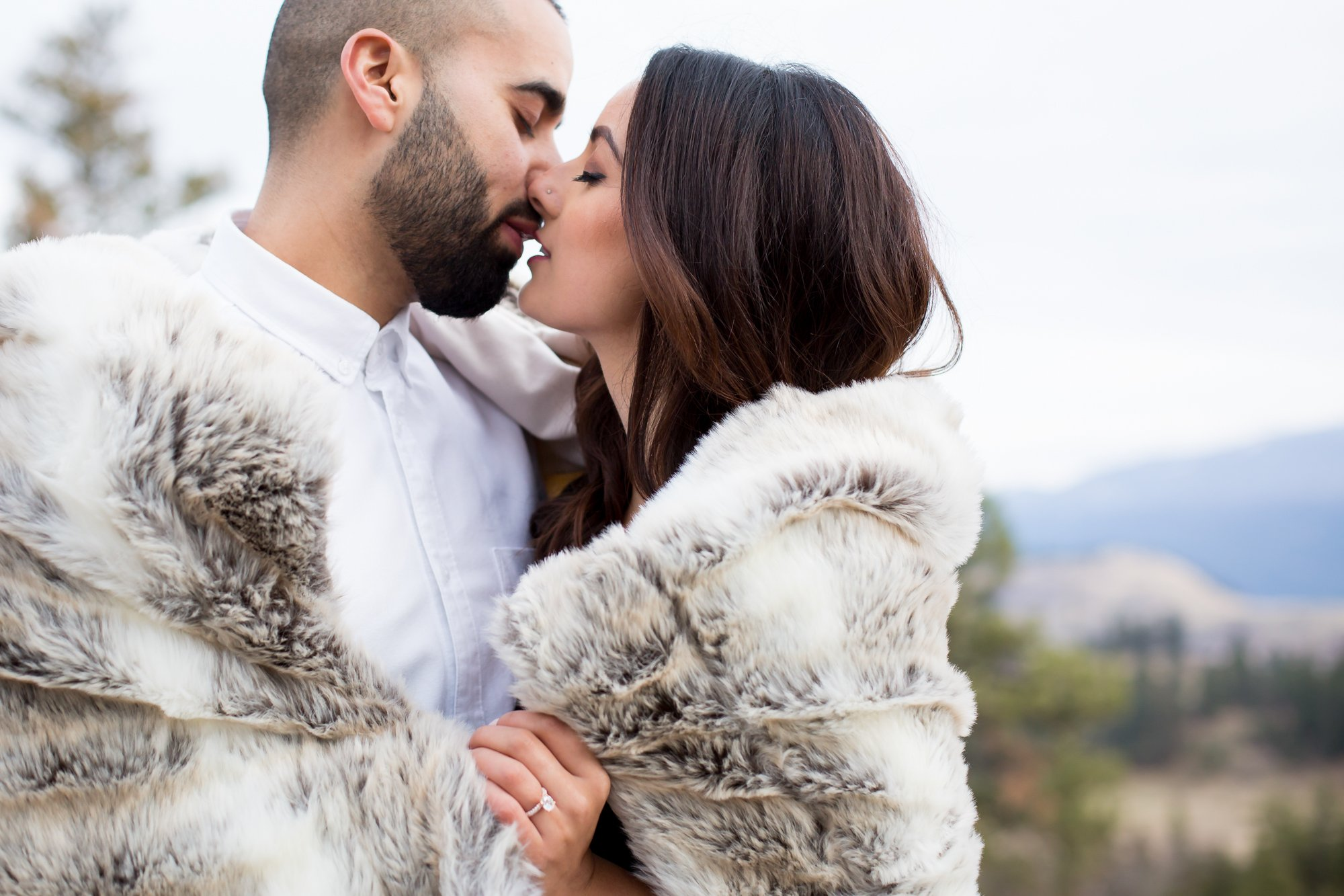 A couple kissing wrapped in a blanket