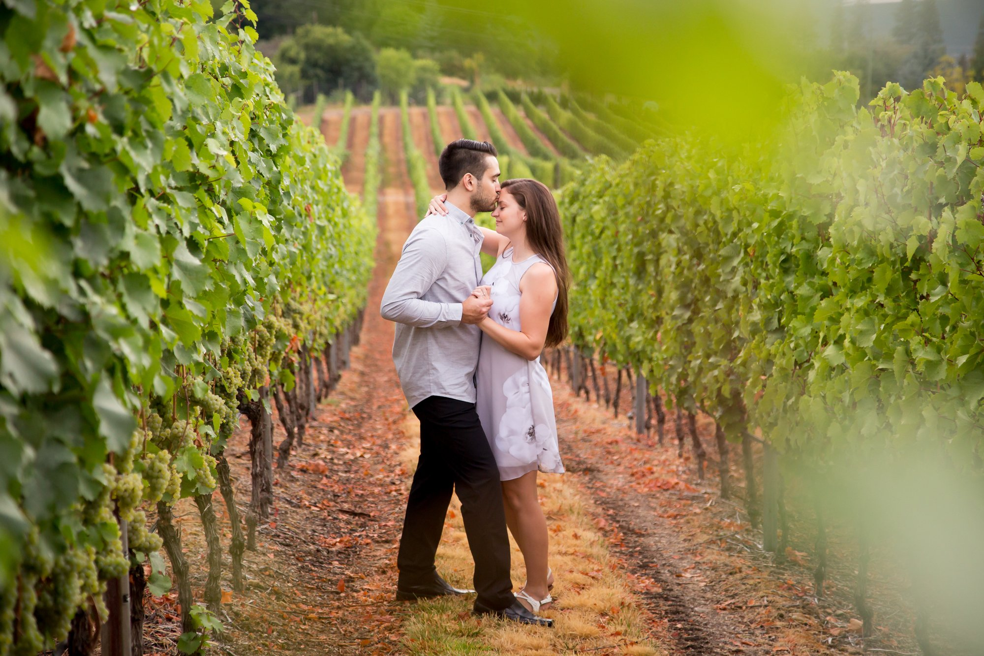 A couple together in a vineyard row