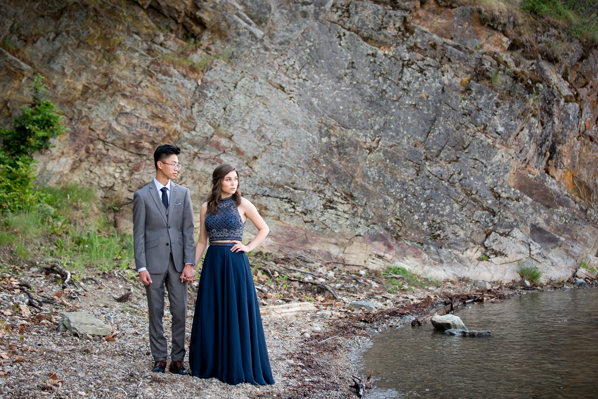 A grad standing lakeside with her date