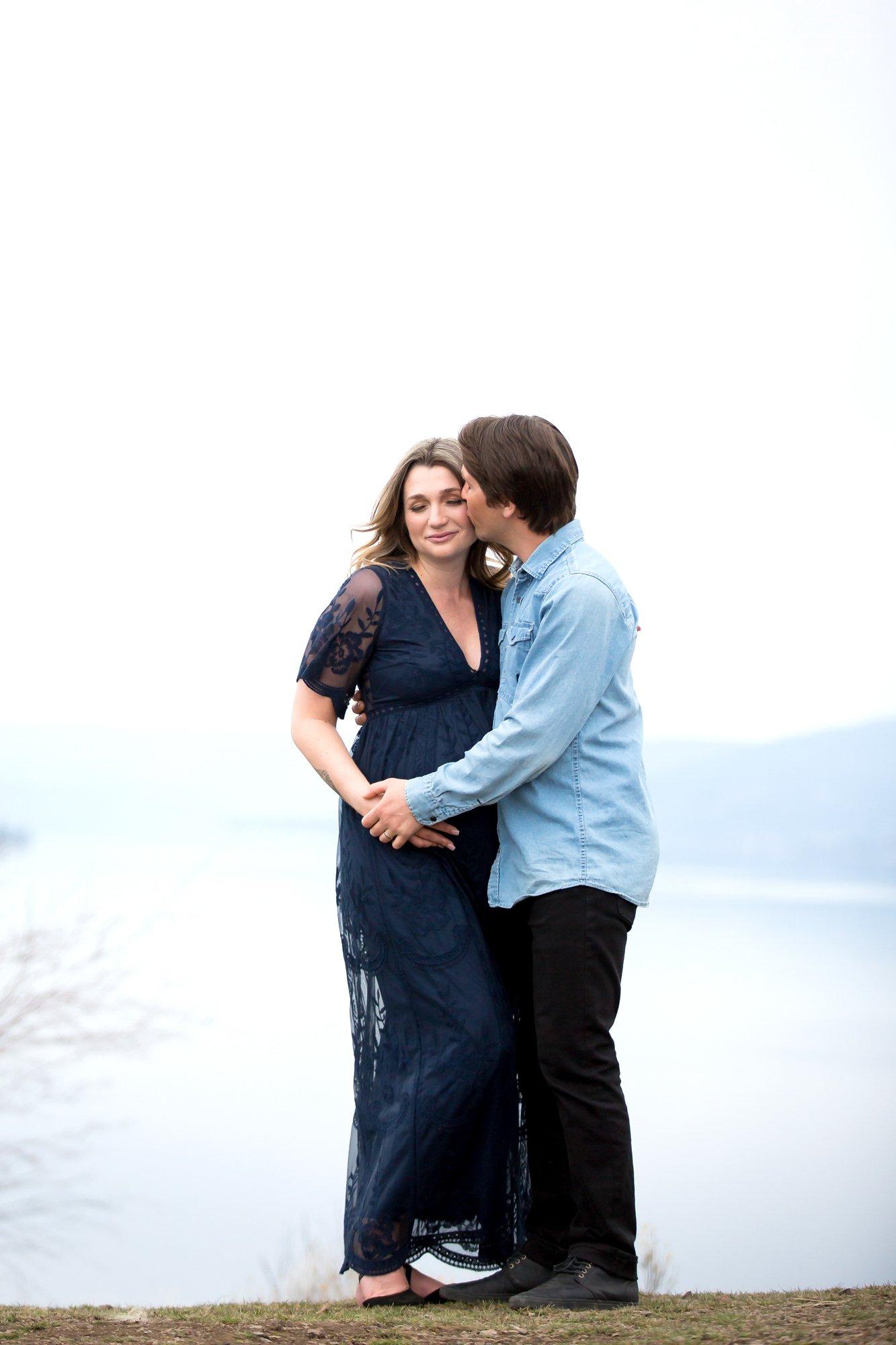 A couple kissing on a mounatin top