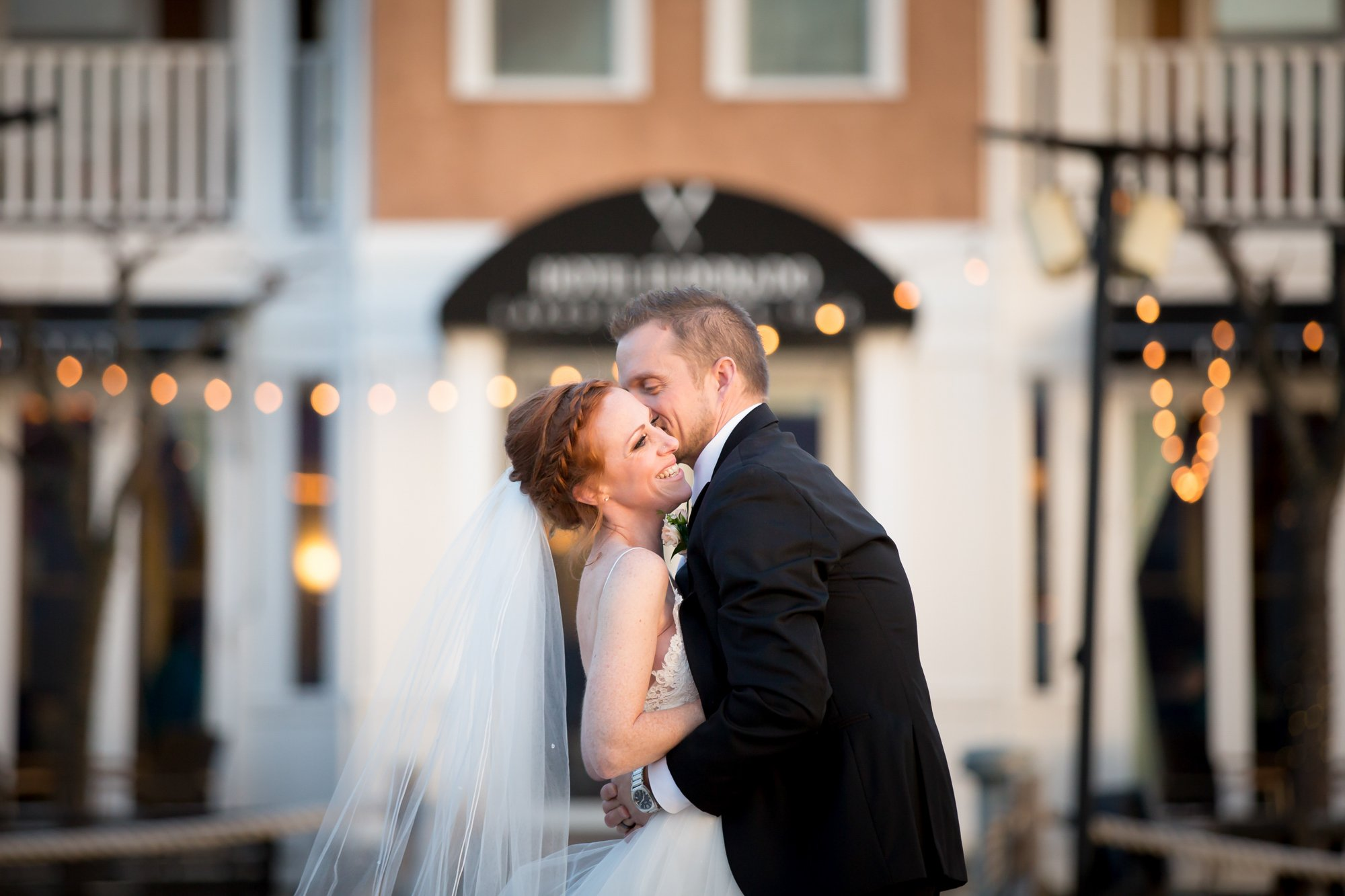 A bride and groom embracing in front of their wedding venue