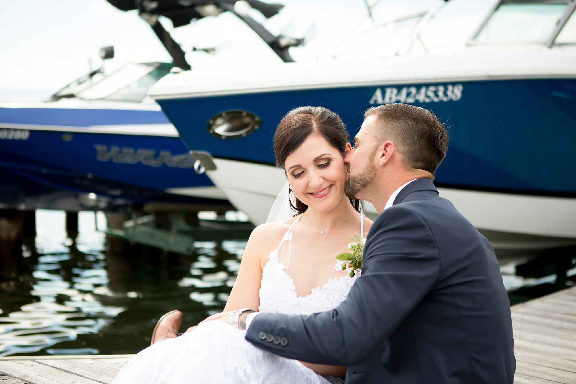 A groom kissing his bride on the cheek in a marina