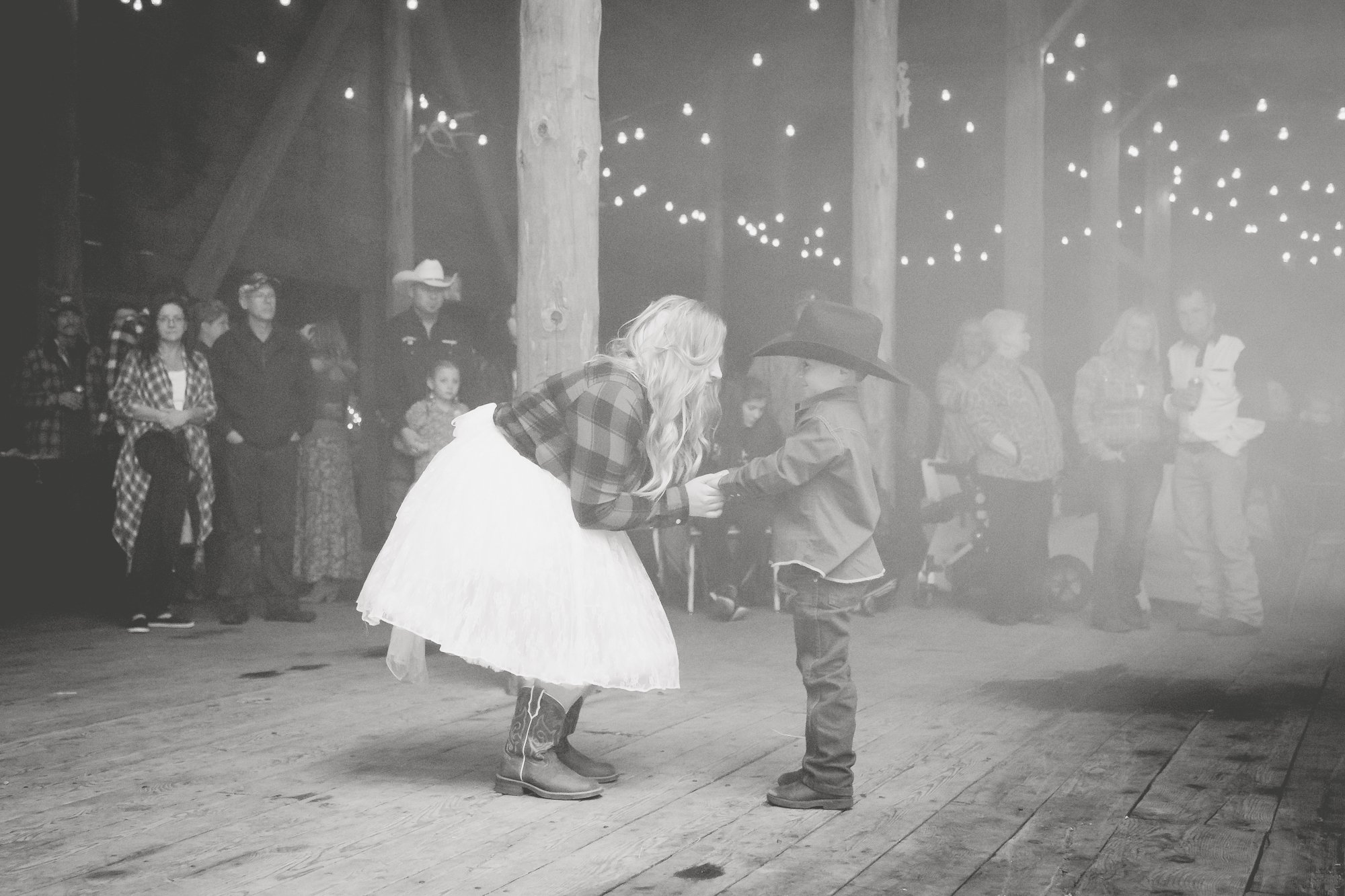 A bride dancing with her son in a barn on her wedding day