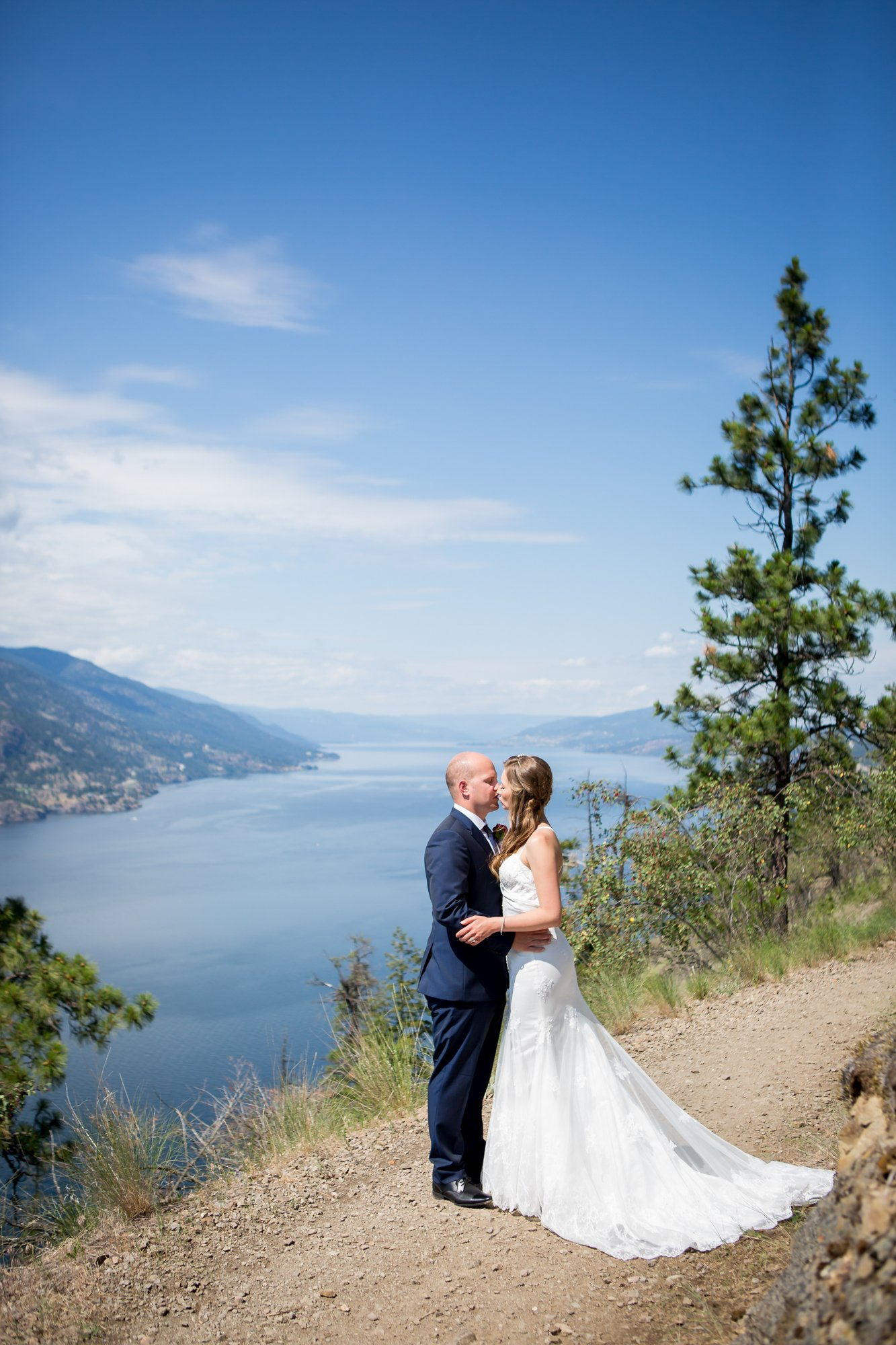 A couple kissing at a viewpoint on their wedding day