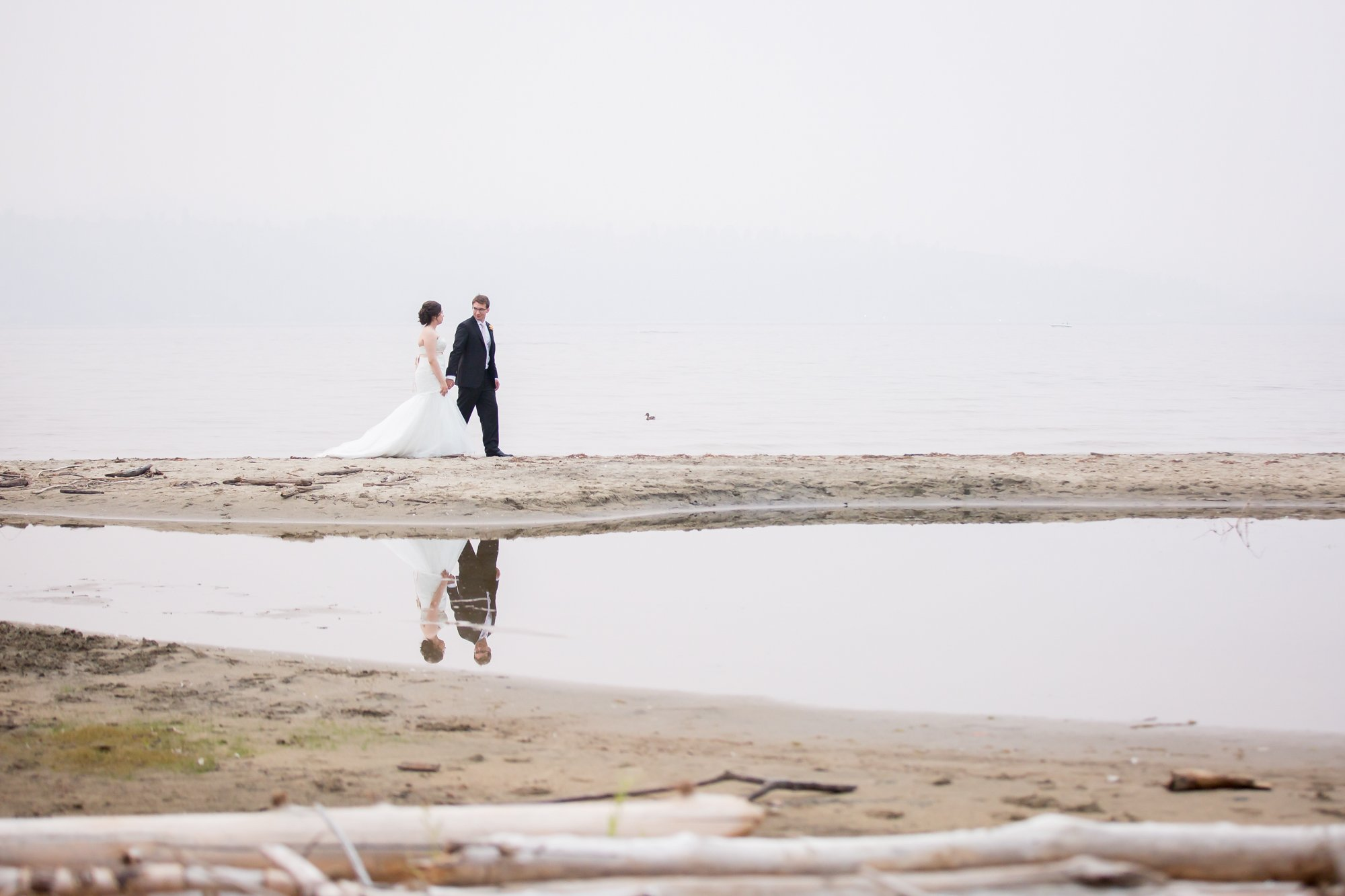 A couple walking along the lakeshore on their wedding day