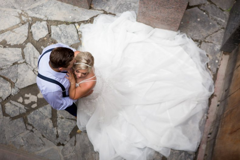 A couple embracing pictured from above with the bride's dress fanned out