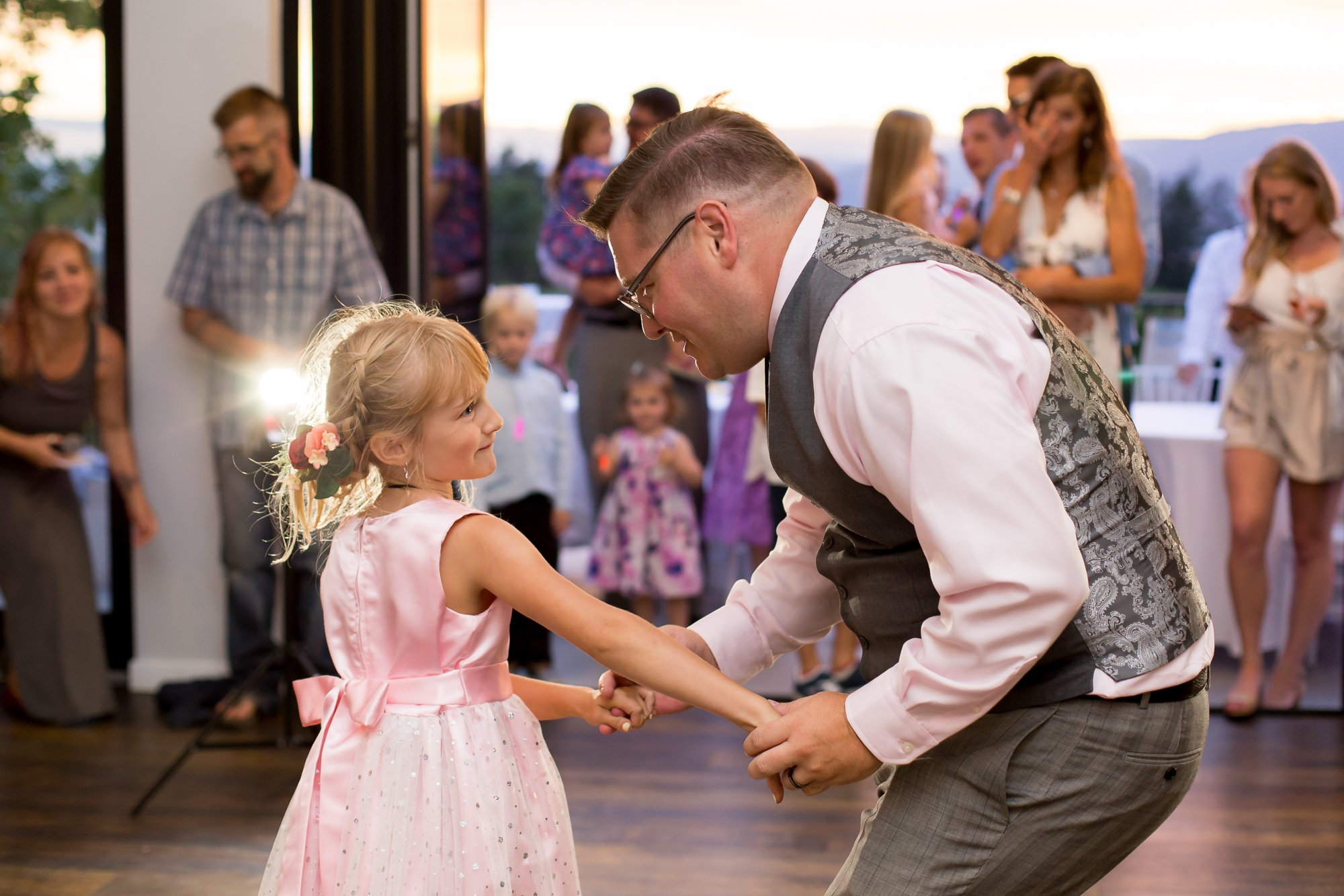 A groom dancing with his daughter