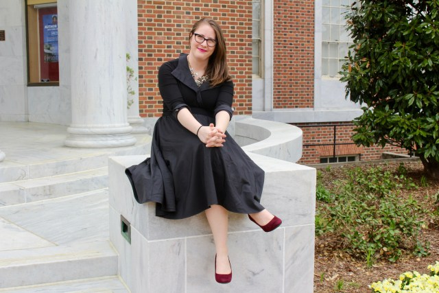 A photo of Ceillie sitting on a stone bench, smiling widely. She is light skinned and has her brown hair down, parted to be on one side of her head. She is wearing a black dress with sleeves that are buttoned up and a large collar, a necklace with intricate crystals, and black cat-eye glasses. Behind her is the brick wall of a building. [Image Description by Lune -https://twitter.com/notstarstuff]​