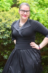 A photo of Ceillie posing with her hands on her hips in front of some greenery. She is light skinned and has brown hair pulled into a ponytail. She is smiling and wearing a black dress with long sleeves, a large collar, and a wide waistband, a necklace with intricate crystals, and black cat-eye glasses. [Image Description by Lune -https://twitter.com/notstarstuff]​