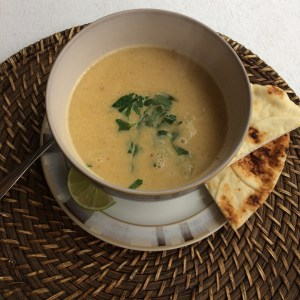 Thai Coconut Cauliflower soup in a bowl with naan and a wedge of lime