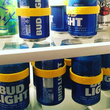 inside view of a fridge shelf full of cans of Bud Light with yellow cando labels on them