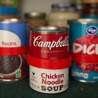 a can of campbells chicken noodle soup on a pantry shelf wearing a CanDo label