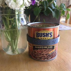 a can of Bush's baked beans wearing a CanDo braille label
