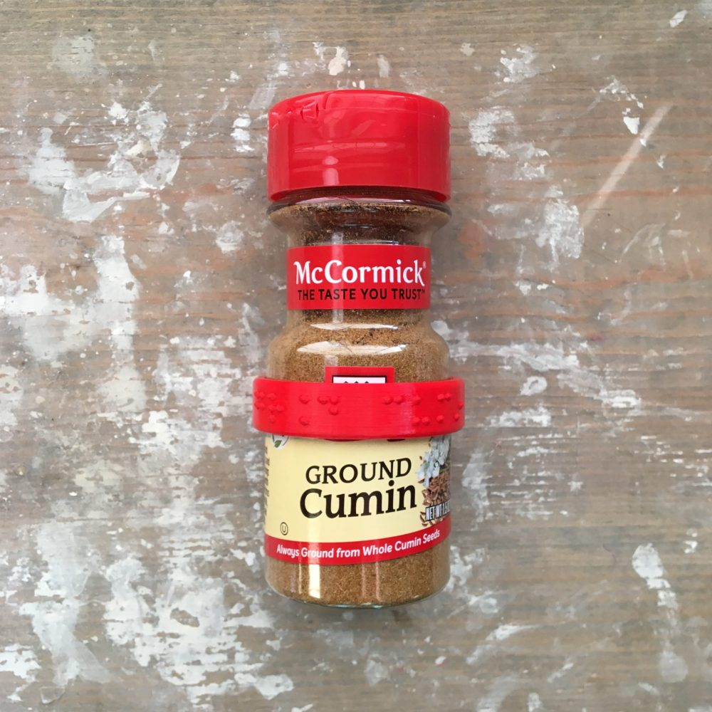 McCormick ground cumin bottle wearing a CanDo braille spice label