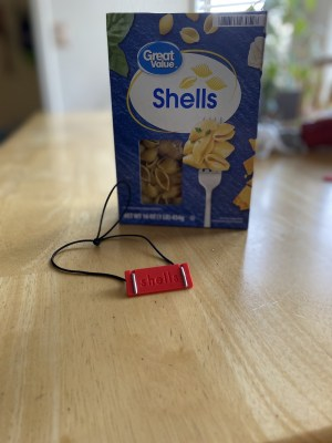 a shells braille label with engraved text on the back next to a shells pasta box