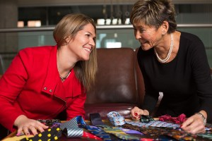 Becky and Rhonda are smiling in front of a table full of custom ties. Becky wears a bold red jacket, and Rhonda wears a black top and pearls.