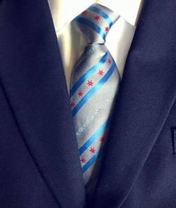 """Closeup of a tie and vest. The tie is silver with the Chicago stars and stripes, with the text """"Chicago Pipe Band,"""""""