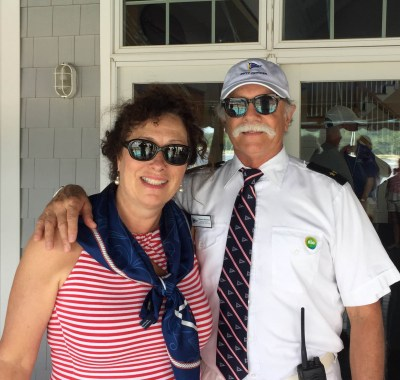 A woman and man stand together smiling, wearing a custom Northport yacht club scarf and tie.