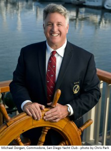 Man stands at a ship steering wheel, smiling, wearing a custom tie and a suit jacket.