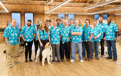 group of people wearing teal blue Hawaiian shirts with the Dental Hero logo in an office with a dog