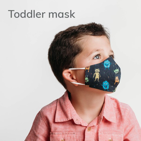 child wearing a toddler size face mask with critters pattern